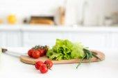 """Постер, картина, фотообои """"томаты и салат листья на разделочную доску в кухне"""""""