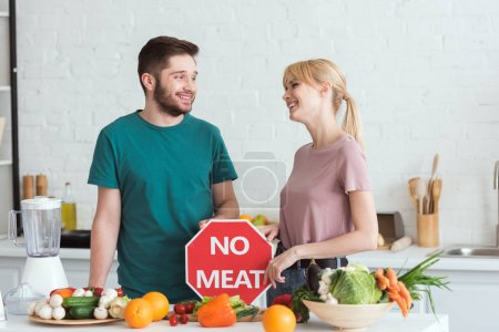 couple of vegans looking at each other with no meat sign in kitchen
