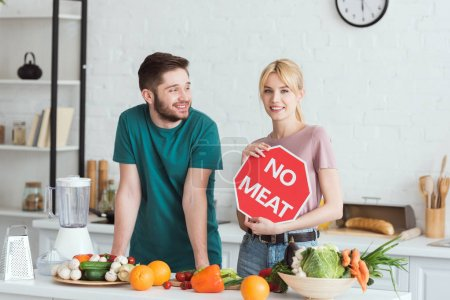 couple of vegans standing with no meat sign at kitchen