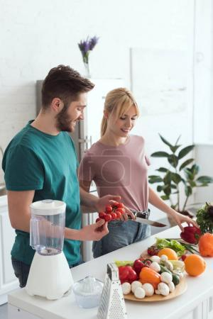 Photo for Smiling couple of vegans cooking at kitchen - Royalty Free Image