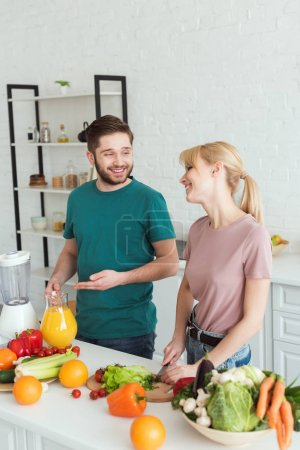 Photo for Couple of vegans smiling and talking while cooking food at kitchen - Royalty Free Image