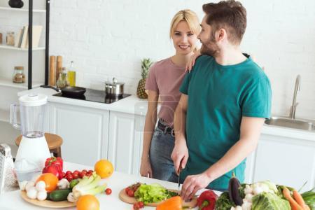 vegan girlfriend hugging boyfriend while he cutting vegetables at kitchen