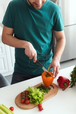 cropped image of man cutting vegetables for vegetarian salad at kitchen