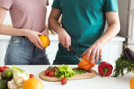 Photo for Cropped image of boyfriend cutting vegetables for vegetarian salad at kitchen - Royalty Free Image