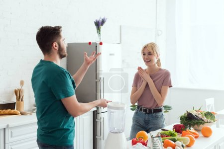 vegan boyfriend juggling with cherry tomatoes for happy girlfriend at kitchen