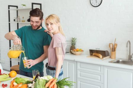 vegan boyfriend pouring fresh juice into glass in kitchen