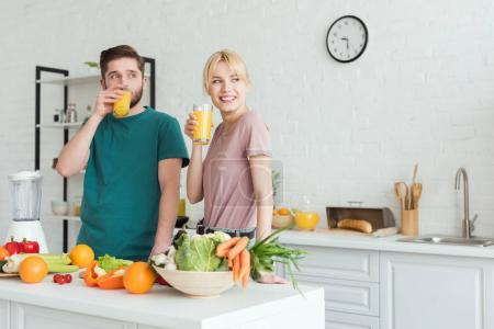 Photo for Smiling couple of vegans drinking fresh juice at kitchen and looking away - Royalty Free Image