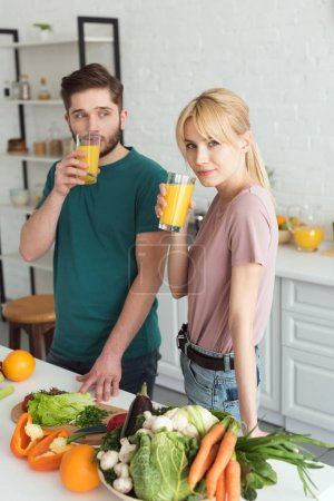 Photo for Couple of vegans drinking fresh juice at kitchen - Royalty Free Image