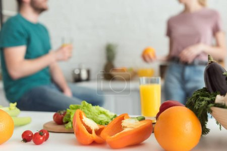 Photo for Cropped image of vegan couple talking in kitchen with fruits and vegetables on foreground - Royalty Free Image