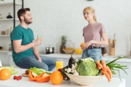 Photo for Vegan couple talking in kitchen with fruits and vegetables on foreground - Royalty Free Image