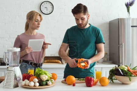 Photo for Couple of vegetarians using tablet with recipe for cooking at kitchen - Royalty Free Image