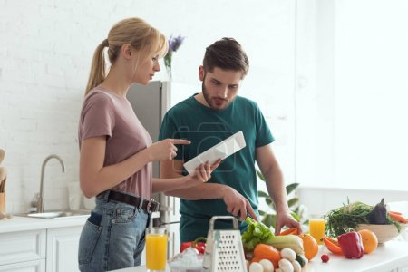girlfriend pointing on tablet with recipe during cooking at kitchen, vegan concept