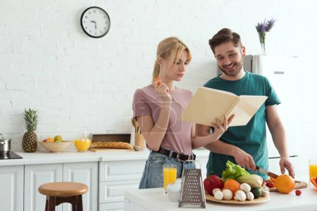 Photo for Couple of vegans preparing salad with recipe book at kitchen - Royalty Free Image