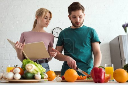 Photo for Couple of vegans preparing food with recipe book at kitchen - Royalty Free Image