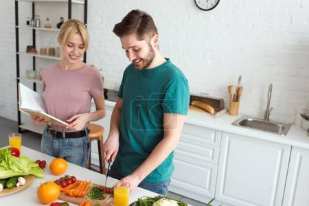 couple of vegans cooking with recipe book at kitchen
