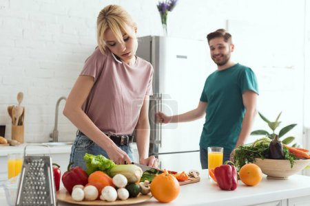 vegan girlfriend talking by smartphone while cooking salad at kitchen