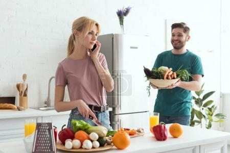 vegan girlfriend talking by smartphone while cooking at kitchen