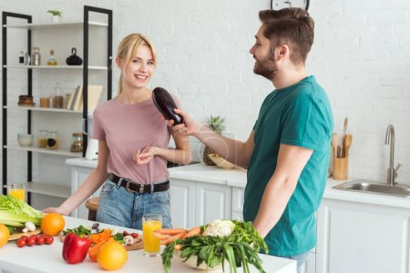 Photo for Boyfriend using eggplant as microphone and having fun at kitchen, vegan concept - Royalty Free Image