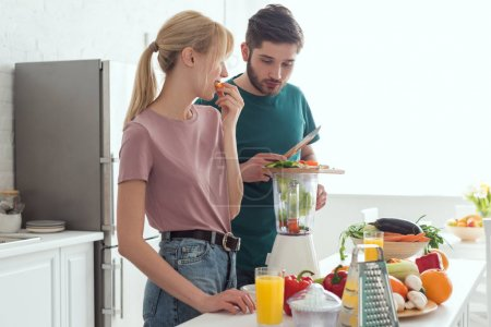 boyfriend preparing vegetable juice with juicer at kitchen, vegan concept