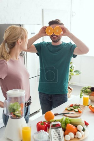 Photo for Boyfriend having fun and covering eyes with orange pieces at kitchen, vegan concept - Royalty Free Image