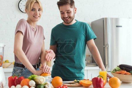 couple de végétaliens préparation jus avec presse-agrumes à la cuisine