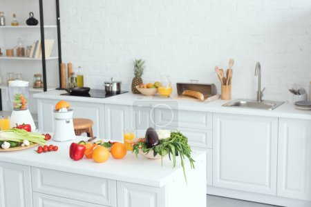Photo for Interior of white modern kitchen with fruits and vegetables on kitchen counter - Royalty Free Image