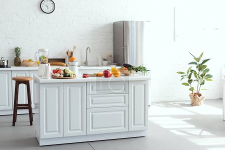 interior of white light kitchen with fruits and vegetables on kitchen counter