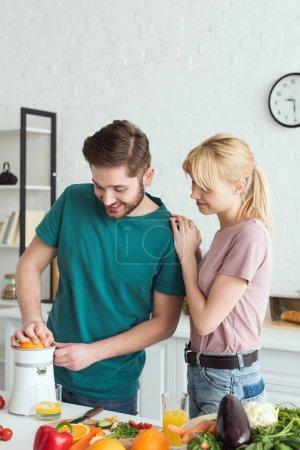 happy boyfriend preparing fresh juice at kitchen, vegan concept