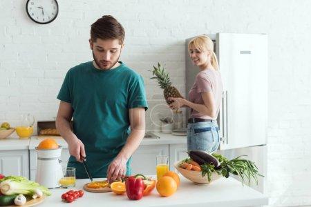 boyfriend cutting fruits for vegan meal at kitchen