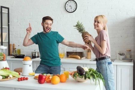 smiling couple of vegans having fun while cooking at kitchen