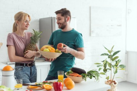 Photo for Young vegan couple with fresh fruits and vegetables in kitchen at home - Royalty Free Image
