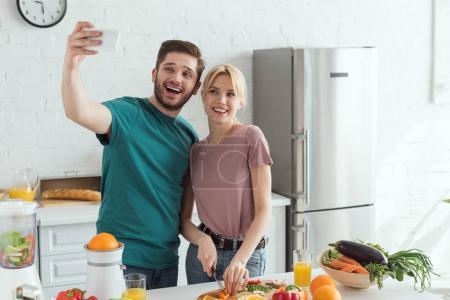 Photo pour Sourire couple végétalien prendre selfie tout en cuisinant ensemble dans la cuisine à la maison - image libre de droit