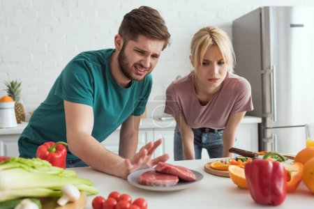 disgusted vegan couple looking at raw meat on plate in kitchen at home