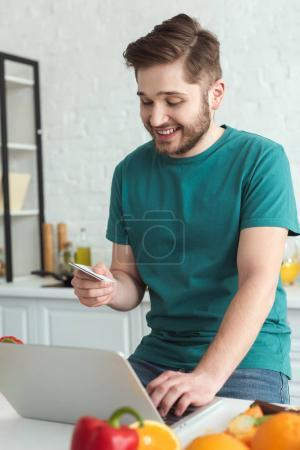 smiling man with credit card and laptop buying goods online in kitchen at home
