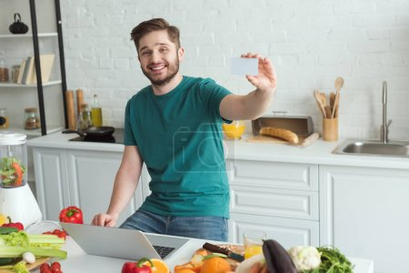 smiling man showing credit card at table with laptop in kitchen at home
