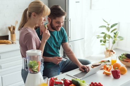 Photo for Vegan couple using laptop together in kitchen at home - Royalty Free Image