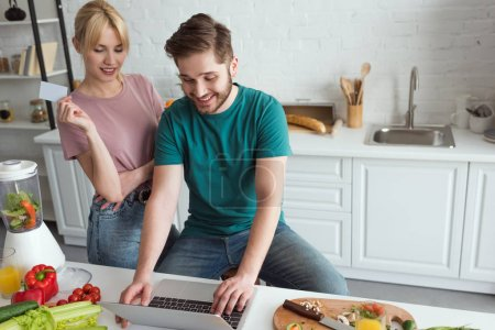 vegan couple with laptop buying goods online together in kitchen at home
