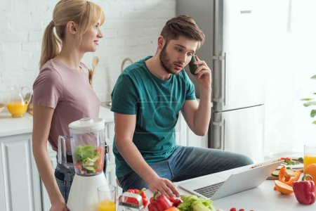 man pretending talking on cucumber at table with laptop and girlfriend near by in kitchen at home, vegan lifestyle concept