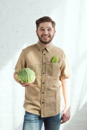 portrait of smiling young man with fresh savoy cabbage in hand, vegan lifestyle concept