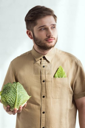 portrait of pensive young man with fresh savoy cabbage in hand, vegan lifestyle concept