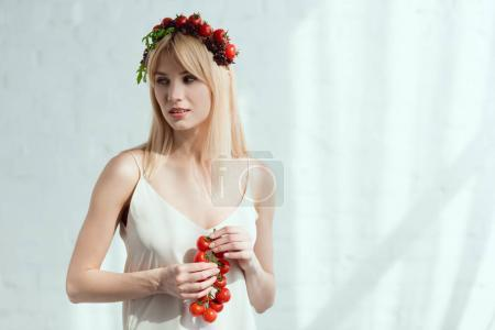 woman with cherry tomatoes in hands and wreath made of fresh lettuce and cherry tomatoes, vegan lifestyle concept