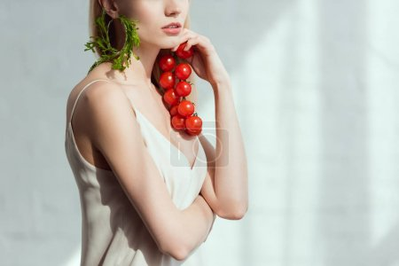 Photo for Partial view of woman with cherry tomatoes in hand and earring made of fresh arugula, vegan lifestyle concept - Royalty Free Image