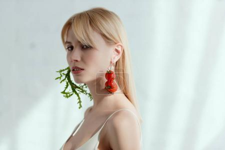 thoughtful woman in dress with earrings made of fresh arugula and cherry tomatoes, vegan lifestyle concept