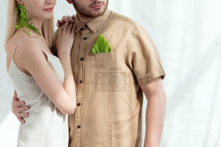 cropped shot of woman with earring made of arugula lean on boyfriend with savoy cabbage leaf in pocket, vegan lifestyle concept