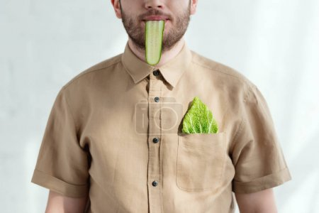 partial view of man with cucumber slice in mouth and savoy cabbage leaf in pocket, vegan lifestyle concept