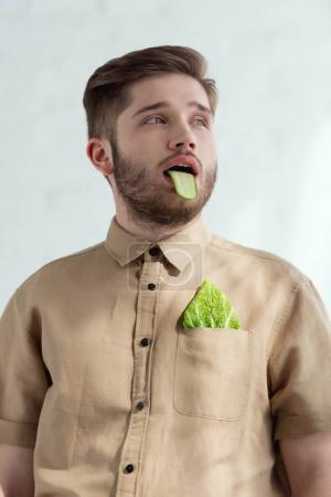 portrait of man with cucumber slice in mouth and savoy cabbage leaf in pocket, vegan lifestyle concept