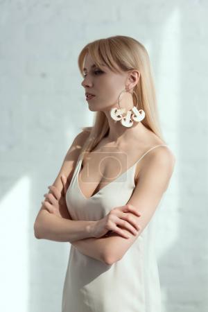 belle femme pensive en robe avec boucle d'oreille fait de champignons, concept de mode de vie végétalien