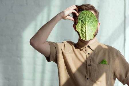 Photo for Obscured view of pensive man with savoy cabbage leaf on face, vegan lifestyle concept - Royalty Free Image