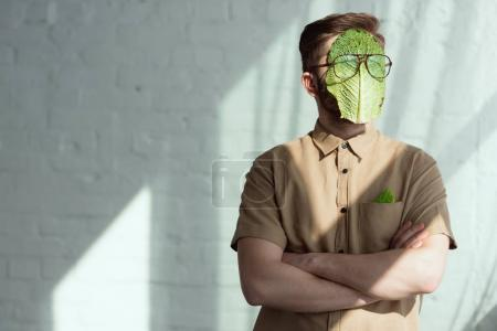 obscured view of man with savoy cabbage leaf and eyeglasses on face, vegan lifestyle concept