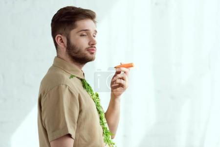Photo for Side view of young man with tie made of arugula and carrot as cigarette, vegan lifestyle concept - Royalty Free Image